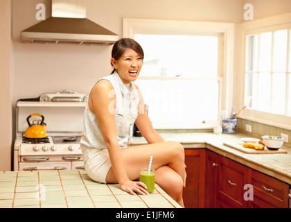 Junge Frau mit grünen Smoothie in Küche - Stockfoto