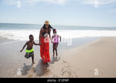 Mutter und Kinder zu Fuß am Strand - Stockfoto