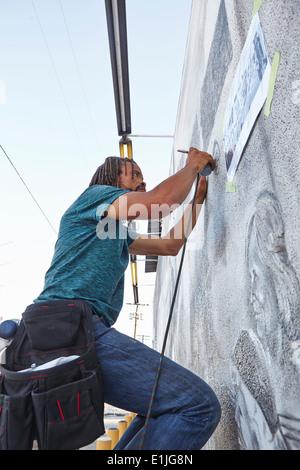 Männlichen Afroamerikaner Airbrush Künstler Malerei Wandbild - Stockfoto