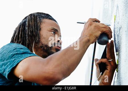 Nahaufnahme eines männlichen Afroamerikaner Airbrush Künstler Malerei Wandbild - Stockfoto