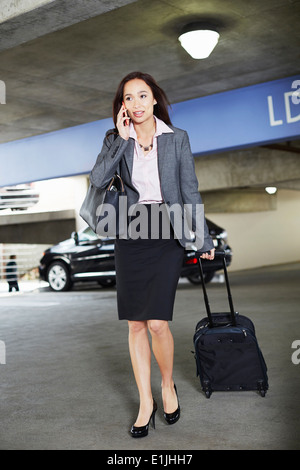 Junge weibliche Unternehmerin mit fahrbaren Koffer auf Parkplatz