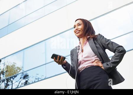 Junge weibliche Unternehmerin mit Smartphone außerhalb Büro - Stockfoto