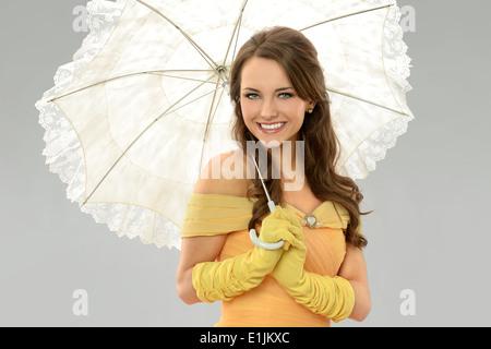 Junge Frau im viktorianischen Kleid Holding Regenschirm auf neutralem Hintergrund isoliert Stockfoto