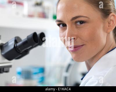 Porträt der Wissenschaftlerin durch ein Mikroskop. - Stockfoto