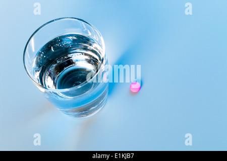 Glas Wasser und einem gelben Pille Studio gedreht. - Stockfoto