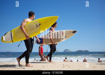 RIO DE JANEIRO, Brasilien - 20. Februar 2014: Paar junge brasilianische Surfer gehen mit Surfbrettern entlang der - Stockfoto