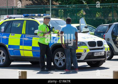 Polizist im Gespräch mit schwarzer Mann von Polizei-Auto. - Stockfoto