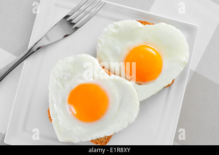 einige herzförmigen Spiegeleier auf Toast in eine Platte, auf einem gedeckten Tisch - Stockfoto