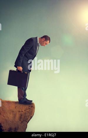 Geschäftsmann in einer Zwangslage, die vor einem Dilemma auf einer Klippe Rand am Abgrund - Stockfoto