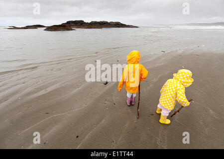 Zwei Kinder in bunten Regen Slickers gekleidet erkunden Wickaninnish Beach, Vancouver Island, British Columbia, - Stockfoto