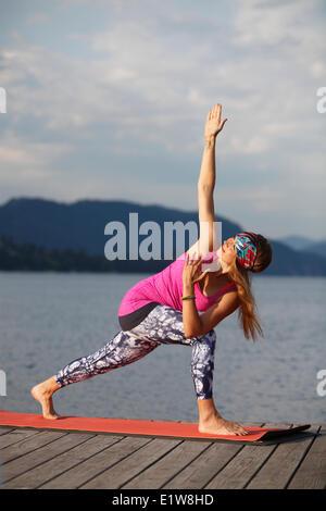 Junge Frau praktizieren Yoga am dock mit Blick auf Kalamalka Lake in der Nähe von Vernon, Okanagan, British Columbia, - Stockfoto