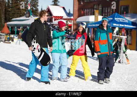 4 junge Erwachsene zu Fuß durch Silver Star Mountain Resort Village in der Nähe von Vernon, Okanagan, British Columbia, - Stockfoto