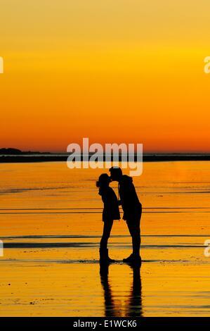 Ein junges Paar bei Sonnenuntergang während auf Chesterman Beach in der Nähe von Tofino, BC zu küssen. - Stockfoto