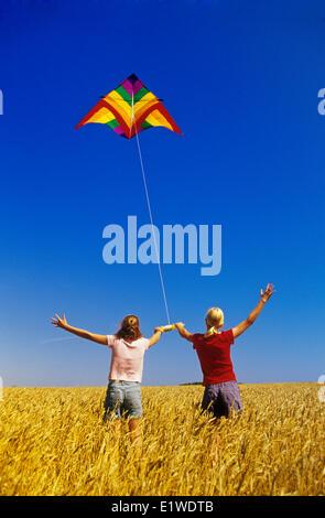 zwei Mädchen in einem Frühling Weizenfeld ein Drachen in der Nähe von Winnipeg, Manitoba, Kanada - Stockfoto