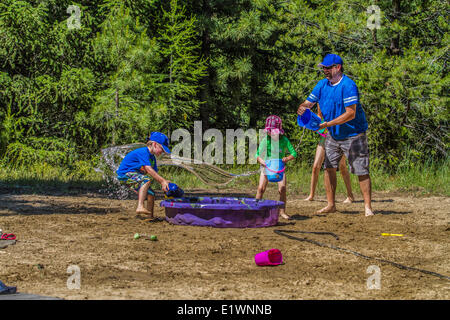 Erwachsene und Kinder in einem spielerisch-Wasser zu kämpfen, an einem warmen, sonnigen Sommertag. Cranbrook, Britisch - Stockfoto