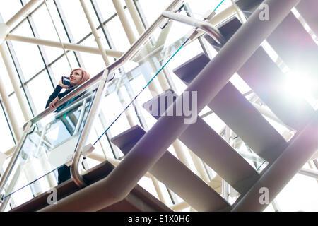 Attraktive Frauen, die auf dem Telefon auf einer Treppe - Stockfoto