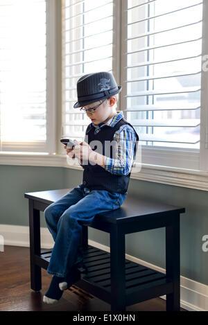 Junge Spiele auf ein Handy - Stockfoto