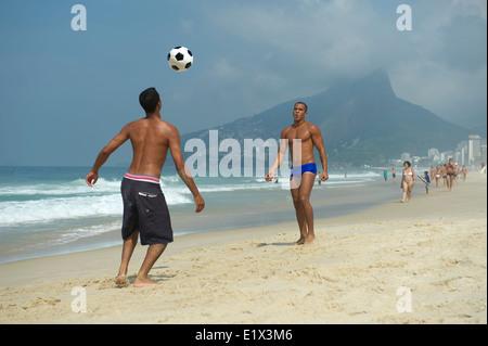 Zwei junge Carioca Brasilianer spielen am Ipanema Strand Rio de Janeiro Brasilien Altinho keepy uppy Strandfußball - Stockfoto