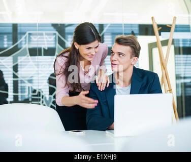 Junger Geschäftsmann mit Kollegin diskutieren über Laptop am Tisch im Büro - Stockfoto