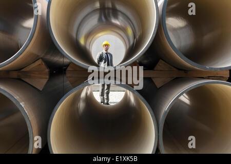 Voller Länge des jungen männlichen Architekten durch gestapelte Rohre auf Baustelle - Stockfoto