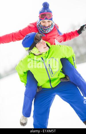 Glücklich Jüngling geben Huckepack Fahrt zur Frau im Schnee