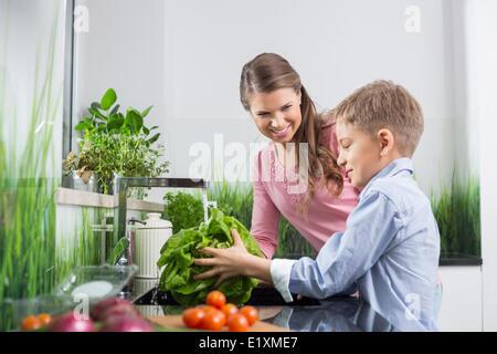 Glückliche Mutter Sohn Waschen von Gemüse in der Küche zu betrachten - Stockfoto