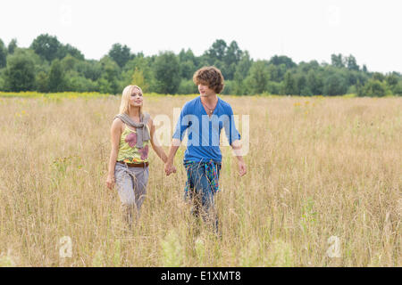 Junges Paar Hand in Hand bei einem Spaziergang durch Feld - Stockfoto