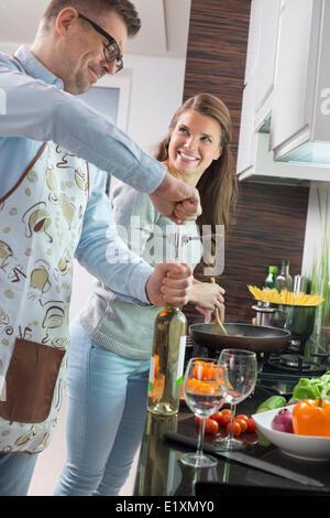 Mann, die Öffnung der Flasche Wein beim Kochen mit Frau in Küche - Stockfoto
