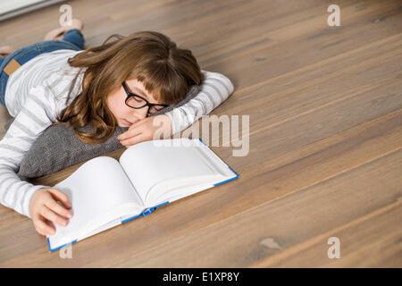 Erhöhte Ansicht von Teenager-Mädchen schlafen während des Studiums auf Etage - Stockfoto