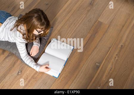 Erhöhte Ansicht des Mädchens Lesebuch im Stock zu Hause - Stockfoto