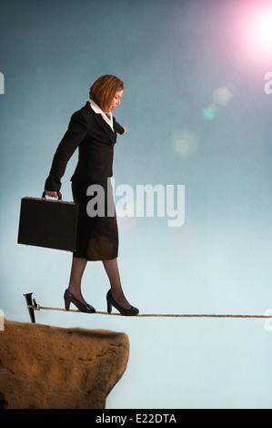 Geschäftsfrau, die auf einem Drahtseil oder Highwire veranschaulicht das Konzept des unternehmerischen Risikos ausgehend - Stockfoto