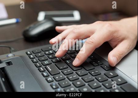 Hand des weißen Mannes Drücken der Enter-Taste auf der Laptoptastatur - Stockfoto