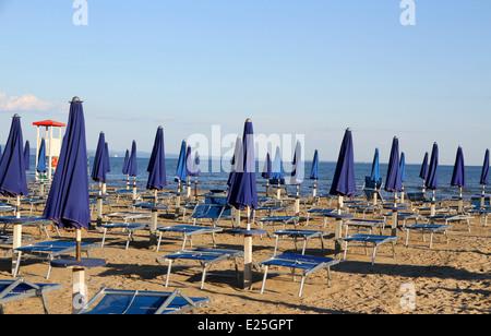 Viele Sonnenschirme und Liegestühle am Strand bei Sonnenuntergang an der Küste mit Aussichtsturm - Stockfoto