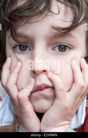 Junge Ruhe Kinn in Händen, gelangweilt Gesichtsausdruck - Stockfoto