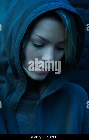 Frau in Sweatshirt mit Kapuze sinnend blickte - Stockfoto