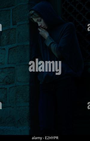 Frau im Sweatshirt mit Kapuze stehen in Tür blickte nachdenklich - Stockfoto