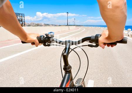 Nahaufnahme eines jungen Mannes, mit dem Fahrrad auf einer nicht befahrenen Straße - Stockfoto