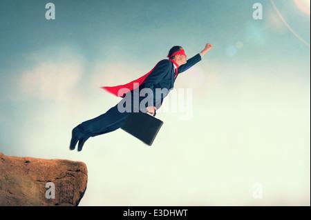Superheld Geschäftsmann um zu Flug von einem Felsvorsprung trägt einen Umhang und Maske - Stockfoto