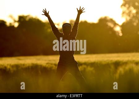 Wenig junge Freiheit springen im Weizenfeld bei Sonnenuntergang - Stockfoto