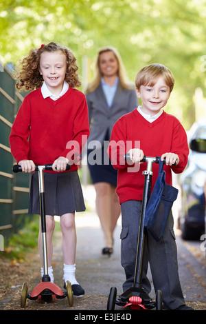 Kinder reiten Roller auf dem Weg zur Schule mit Mutter - Stockfoto