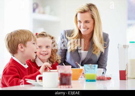 Mutter und Kinder frühstücken In der Küche zusammen - Stockfoto