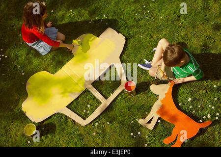 Kinder malen Karton Cut Outs im Garten Stockfoto