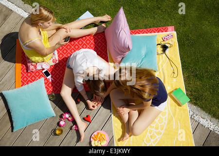 Mädchen im Teenageralter Hanging Out in Garten, erhöht, Ansicht Stockfoto