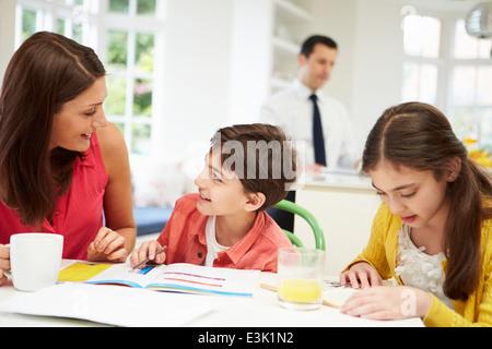 Mama hilft Kindern bei den Hausaufgaben, wie Papa im Hintergrund arbeitet - Stockfoto