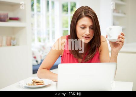 Hispanic Frau mit Laptop In der Küche zu Hause - Stockfoto