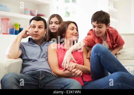 Hispanische Familie sitzt auf dem Sofa vor dem Fernseher zusammen - Stockfoto