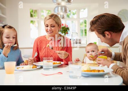 Familie mit Kleinkind Essen Mahlzeit zu Hause - Stockfoto