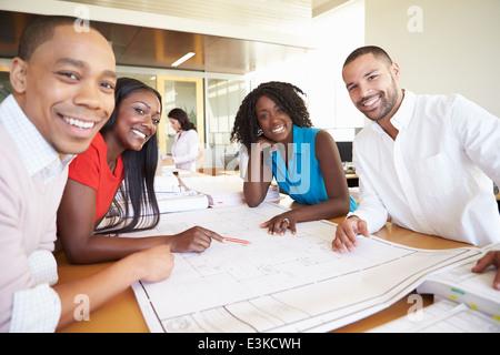 Architektengruppe diskutieren Pläne im modernen Büro - Stockfoto