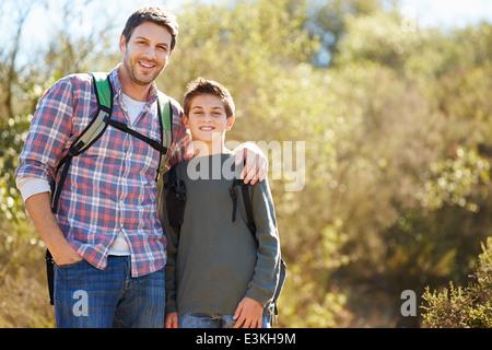 Vater und Sohn wandern im Land tragen Rucksäcke - Stockfoto