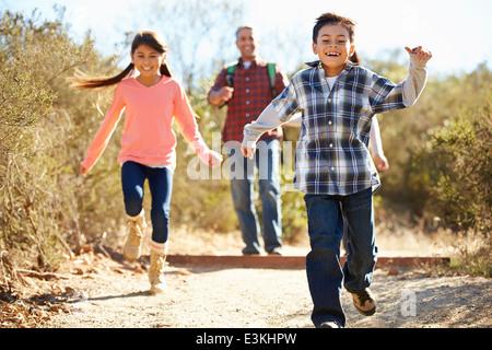 Vater und Kinder Wandern im Land tragen Rucksäcke - Stockfoto